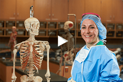 OCC student in surgical scrubs, next to a skeletal model.