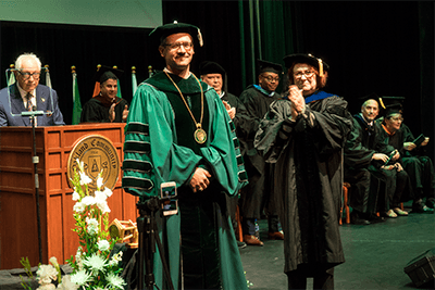 OCC's 9th Chancellor Peter M. Provenzano Jr standing on stage surrounded by staff, faculty, students and the community.