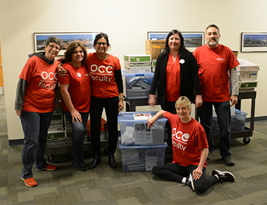 Oakland Community College Faculty surrounded by school supplies they donated to the Pontiac Education Association.