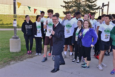 OCC Chancellor posing in front of OCC students before the start of the 5K.